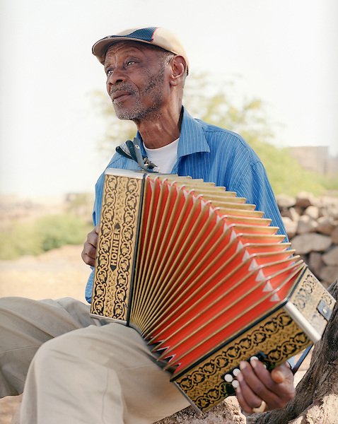 """Grigorio Viaz nicknamed """"Code de Dona"""" ( Grandmothers's favorite) sits outside his home in Sao Francisco playing his accordion.  Music and dance are a focal point of Cape Verdean culture. The most popular traditional music and dance type is morna. Lyrics are usually in Cape Verdean Creole, and instrumentation often includes cavaquinho, clarinet, accordion, violin, piano and guitar. Morna is considered the national music of Cape Verde."""
