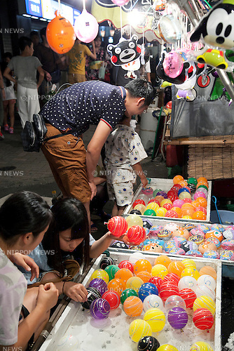 "July 8, 2014, Tokyo, Japan - Children enjoy playing at the ""Iriya Asagao-ichi Market Festival"" on July 8, 2014. The market festival was the most famous for asagao plants (morning glories) in Edo period, and has been held on July 6, 7, and 8 at the Temple of Iriya Kishimojin in Tokyo every year since late Edo period. The flower was introduced into Japan 1200 year ago from China for medical uses. (Photo by Rodrigo Reyes Marin/AFLO)"