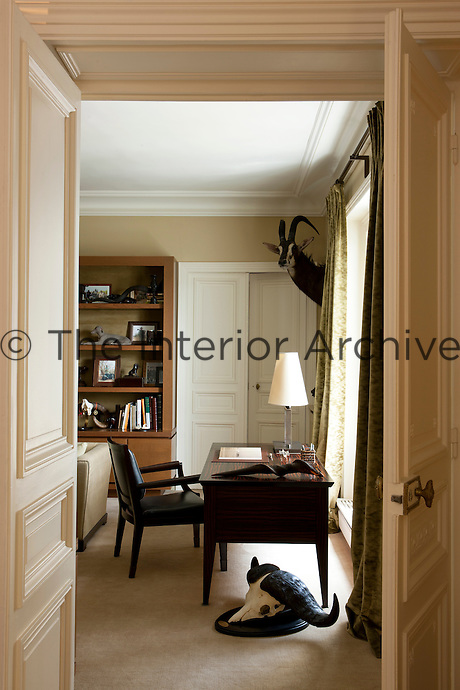 The study/sitting room is decorated with a collection of hunting trophies and furnished with an ebony desk