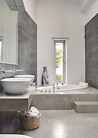 Large grey Porcelanosa tiles line the walls of the bathroom complementing the tones of the concrete floor