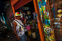 """José Corredor (""""Runner"""") talks on the phone in front of a storage room of the sign painting workshop in Cartagena, Colombia, 16 April 2018. Hidden in the dark, narrow alleys of Bazurto market, a group of dozen young men gathered around José Corredor (""""Runner""""), the master painter, produce every day hundreds of hand-painted posters. Although the vast majority of the production is designed for a cheap visual promotion of popular Champeta music parties, held every weekend around the city, Runner and his apprentices also create other graphic design artworks, based on brush lettering technique. Using simple brushes and bright paints, the artisanal workshop keeps the traditional sign painting art alive."""