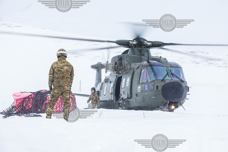 British soldiers on a helicopter mission to transport firewood to a remote Norwegian cabin. The newly built Vouma cabin in Dividalen National Park is part of the Norwegian Trekking Association network. As a goodwill gesture and part of their Arctic training the Royal Navy use helicopters to fly firewood to the remote location. <br /> <br /> <br /> In 2019 the Arctic exercise Clockwork passed 50 years of training in Norway, and now has a permanent base within the Norwegian Air Force base at Bardufoss. <br /> <br /> 845 Naval Air Squadron is a squadron of the Royal Navy's Fleet Air Arm. Part of the Commando Helicopter Force, it is a specialist amphibious unit operating the Leonardo Commando Merlin Mk3 helicopter and provides troop transport and load lifting support to 3 Commando Brigade Royal Marines.<br /> <br /> ©Fredrik Naumann/Felix Features