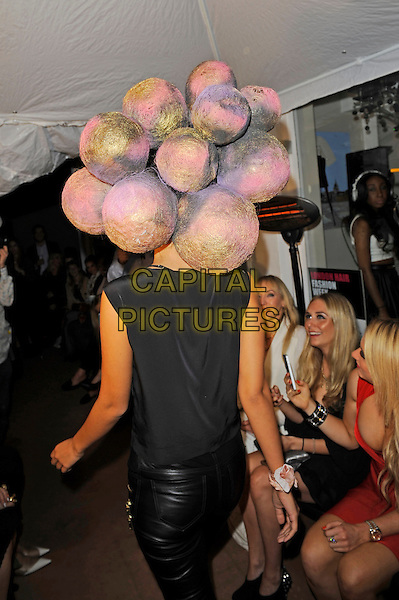 Model<br /> The Tatiana Hair Extensions LFW Avant Garde Catwalk Collection, Tatiana Hair Extensions, Kensington, London, England. <br /> 11th September 2013<br /> fashion week half length black top leather trousers balls baubles back behind rear <br /> CAP/MAR<br /> &copy; Martin Harris/Capital Pictures