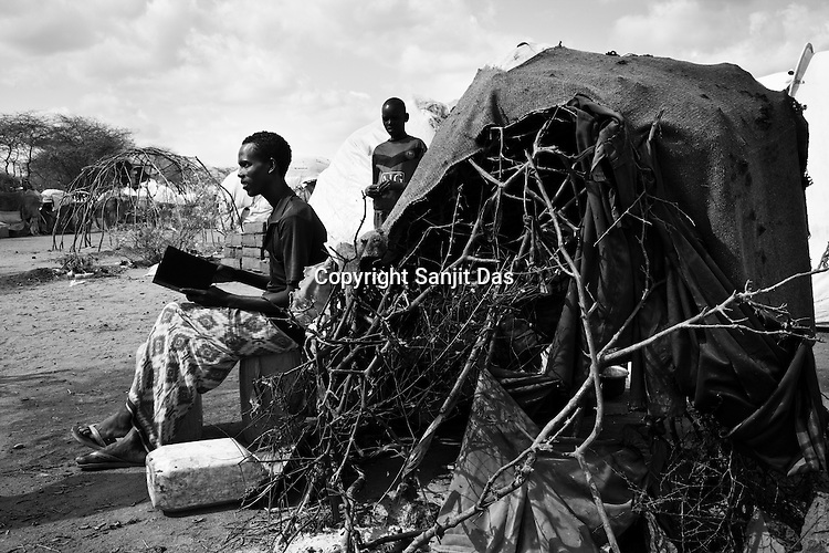 A young Somali man is seen reading the Holy Quran outside his hut in  the Dagahaley refugee camp in the Dadaab refugee camp in northeastern Kenya. Hundreds of thousands of refugees are fleeing lands in Somalia due to severe drought and arriving in what has become the world's largest refugee camp. Photo: Sanjit Das/Panos