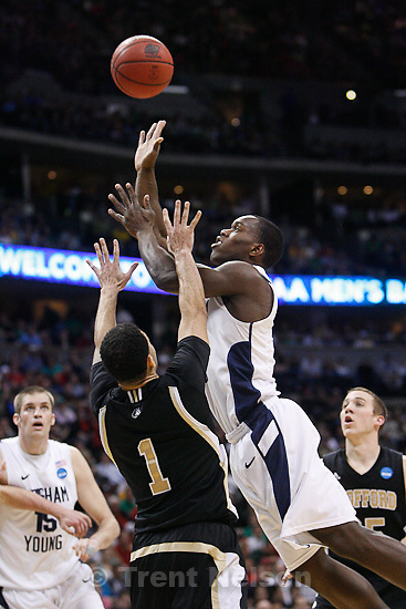 Trent Nelson  |  The Salt Lake Tribune.BYU's Charles Abouo shoots the ball over Wofford's Cameron Rundles in the second half as BYU faces Wofford in the NCAA Tournament, men's college basketball at the Pepsi Center in Denver, Colorado, Thursday, March 17, 2011.