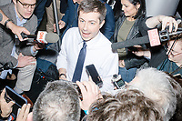 Democratic presidential candidate Pete Buttigieg speaks to the media during an avail at a campaign event at the Currier Museum of Art in Manchester, New Hampshire, USA, on Fri., Apr. 5, 2019. The venue was filled to capacity about an hour before the candidate's arrival, so Buttigieg delivered an impromptu speech to those denied entry outside the museum before the official event. Buttigieg is the mayor of South Bend, Indiana, and was widely considered a long-shot candidate until his appearance in a CNN town hall in March 2019 which catapulted his campaign to prominence and substantial donations. Buttigieg campaign Communications Adviser Lis Smith can be seen in the background.