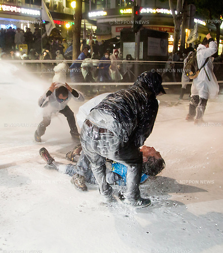 "Protest against Park Geun-Hye, Nov 14, 2015 : People help Baek Nam-gi (bottom), 68, a farmer from Boseong, who fell down after being hit by a direct blast from a police water cannon during an anti-government protest in central Seoul, South Korea. Policemen continued to fire the water cannon containing capsaicin toward the farmer while he was receiving assistance. Baek remains unconscious at a Seoul hospital. ""The People's Camp for Rising Up and Fighting"", representing various groups of farmers, students, workers and the poor, demonstrated on November 14, 2015 to oppose South Korean President Park Geun-Hye's regime to change the labor market and monopolize the authorship of history textbooks. Policemen set up vehicle barriers and fired water cannon to disperse protesters. The organizer said 130,000 people participated in the demo, while the police estimated that 68,000 attended. (Photo by Lee Jae-Won/AFLO) (SOUTH KOREA)"