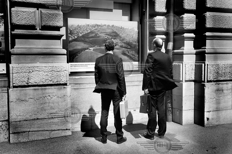 Two businessmen looking at an advertisement for Credit Suisse displayed in the window of a bank on Paradeplatz, the centre of the Swiss banking industry. /Felix Features