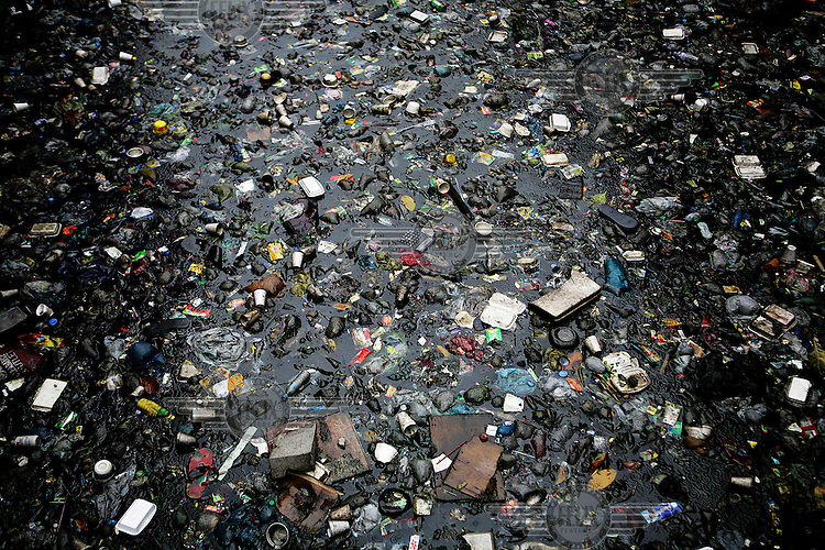 Rubbish floating in a river. Poor families rely on the river for drinking water.