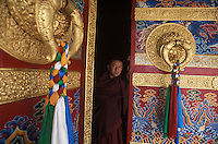 Tibet, Kham<br /> Monk  at monastery doors of new stupa in Kandze.