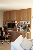The office, tucked into the corner of the living room, is a simple and functional area, distinguished as a self contained work space by the natural wood panelling