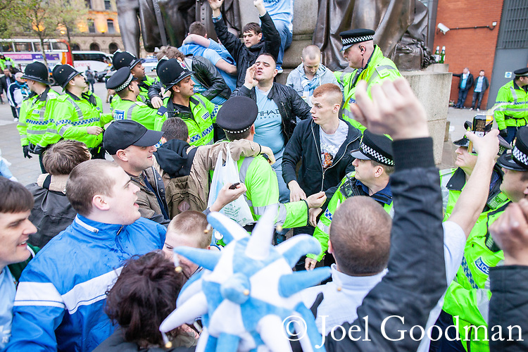 © Joel Goodman - 07973 332324 . 13/05/2012 .  Manchester , UK . Police move in after Manchester City Football Club fans climb a statue of Wellington and wrap a scarf around its neck during celebrations in Piccadilly Gardens in Manchester City Centre after MCFC wins the Premiership title . Photo credit: Joel Goodman