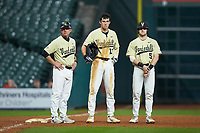 Vanderbilt Commodores head coach Tim Corbin, Connor Kaiser (12) and Philip Clarke (5) stand at third base during a break in the action against the Houston Cougars during game nine of the 2018 Shriners Hospitals for Children College Classic at Minute Maid Park on March 3, 2018 in Houston, Texas. The Commodores defeated the Cougars 9-4. (Brian Westerholt/Four Seam Images)