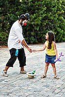 A clown gives balloon to a little girl in the streets of Athens, Greece