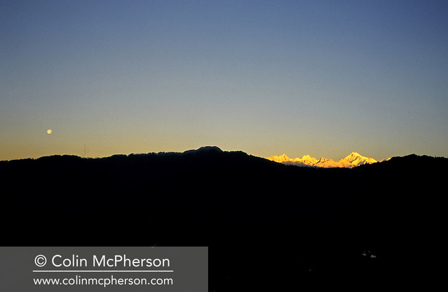 Clear skies at dawn above Kangchenjunga, as seen from Gangtok, Sikkim, northern India. Also known as Sewa Lungma, it was the third highest mountain in the world (after Mount Everest and K2) with an altitude of 8,586 metres (28,169 feet) and was generally regarded as the highest mountain in India and the second highest peak in Nepal. Kangchenjunga translated means The Five Treasures of Snows, as it contained five peaks, four of them over 8,450 metres.