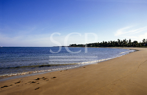 Itaparica Island, Bahia State, Brazil. Sandy beach with palm trees to the right.