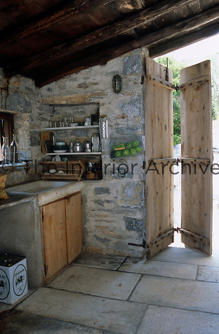 Shelves for untensils and crockery are buit into the stone wall of the simple kitchen