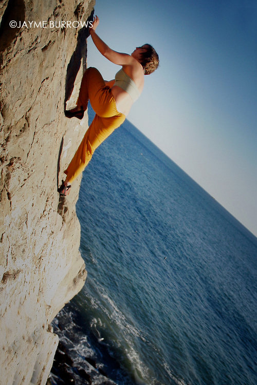 A female climber ascends the face of a rock.