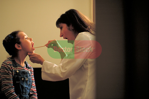 doctor examining young girl's throat with tongue depressor