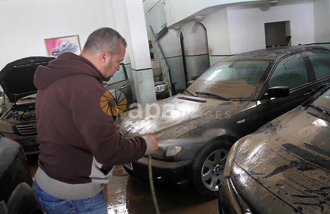 A Palestinian man cleans his cars at car showroom in Gaza City, Dec. 21, 2013. Rescue workers evacuated thousands of Gaza Strip residents from homes flooded by heavy rain, using fishing boats and heavy construction equipment to pluck some of those trapped from upper floors. Photo by Mohammed Asad
