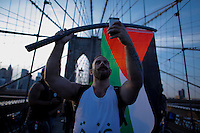 New York City, NY. 20 August 2014. A man holds a Flag as he takes part during a Pro-palestine Rally across de Brooklyn Bridge in Manhattan.  Photo by Kena Betancur/VIEWpress