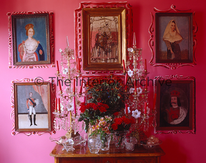 In the bright pink dining room a series of antique portraits is displayed around a flamboyant arrangement of flowers flanked by a pair of ornate crystal candelabra