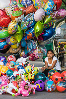 Oaxaca, Mexico, North America.  Day of the Dead Celebrations.  Indian Girl Balloon Vendor, Zocalo, Town Square, Plaza de Armas.