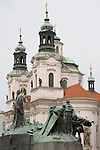 Jan Hus Memorial and St Nicholas Church in the background in the Old Town Square in Prague, Czech Republic.