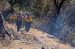 September 13, 2004 Buck Meadows --Tuolumne Fire –- U.S. Forest Service crew hikes past site of burnover near Lumsden Bridge on the Tuolumne River, Stanislaus National Forest. The Tuolumne Fire was a small very fast-moving fire that started around noon on September 12, 2004 near Lumsden Bridge at the bottom of the Tuolumne River.  The fire moved rapidly up the 80-plus-degree slope catching Cal Fire Helitack firefighters, tragically killing firefighter Eva Marie Schicke and injuring five others.