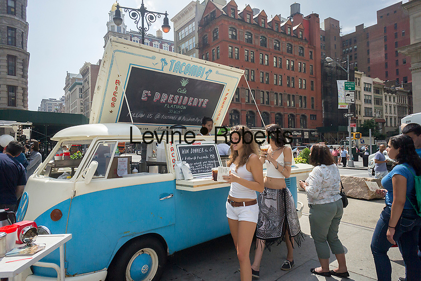 Customers wait on line in front of a converted Volkswagon Minibus to be served a free cup of coffee from Cafe El Presidente during a promotional event for the restaurant on Tuesday, August 5, 2014 in Madison Square in New York. Because of heavy foot traffic the Madison Square pedestrian plazas are popular with event and public relations firms for promotional events for their clients.(© Richard B. Levine)