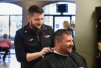 """Stylist Jon Danger (left) gives a haircut to Nick Willbanks of Fayetteville (right), Monday, March 23, 2020 at Sports Clips Haircuts in Fayetteville. Check out nwaonline.com/200323Daily/ for today's photo gallery.<br /> (NWA Democrat-Gazette/Charlie Kaijo)<br /> <br /> Monday is the last day that hair salons, tattoo shops, nail salons and massage parlors are permitted to stay open. He said he heard the news while watching Gov. Asa Hutchinson's address to the state. <br /> <br /> """"[It] sucks man. My job and security. Still got bills to pay. [It's] the unknown of when we're coming back. I'm on a weird fence of do I need a job? Or do I want people to die?"""" he said."""