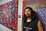 Massapequa, New York, USA. September 18, 2014. MANUEL ADOLFO VILLALOBOS, artist and founding member of the Alternative Hop-Hop group A Side of Darkness A.S.O.D. is next to his colorful paint on canvas Roseland Juxtapoze during the Studio 5404 Art Space opening reception for art show Taking it to the Street. The show features new works by emerging and up-and-coming local and New York artists. Studio 5404 is on the South Shore of Long Island.