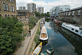 Houseboats on the Grand Union canal and highrise blocks of De Beauvoir Estate, Hackney. The number of people living on London canals has risen sharply as a result of rising rents and property prices.