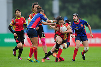 Xu Yang of PR China takes on the Spain defence. FISU World University Championship Rugby Sevens Women's 7th/8th place match between Spain and PR China on July 9, 2016 at the Swansea University International Sports Village in Swansea, Wales. Photo by: Patrick Khachfe / Onside Images