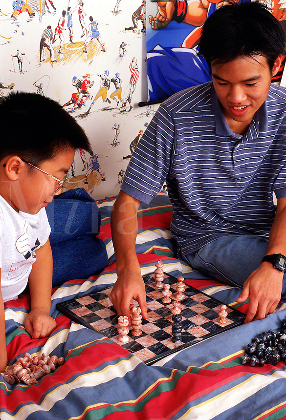 Two Asian-American teenagers play chess in a bedroom.