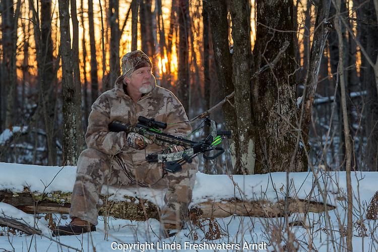 Crossbow hunter sitting on a log