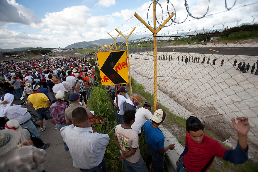5 July 2009 - Tegucigalpa, Honduras - Supporters of ousted Honduras' President Manuel Zelaya wait at a border fence of the international airport in Tegucigalpa. Zelaya turned back from an attempted return home on Sunday after soldiers clashed with his supporters as he tried to land, fueling tensions over the coup that toppled him. At least one person was killed and ten were badly wounded when protesters demanding the return of ousted Honduran President Manuel Zelaya clashed with troops at the Tegucigalpa airport. Photo credit: Benedicte Desrus