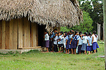 Children in uniform line up to enter their thatched classroom in Midway village, southern Belize.  Midway is a traditional Mayan village.