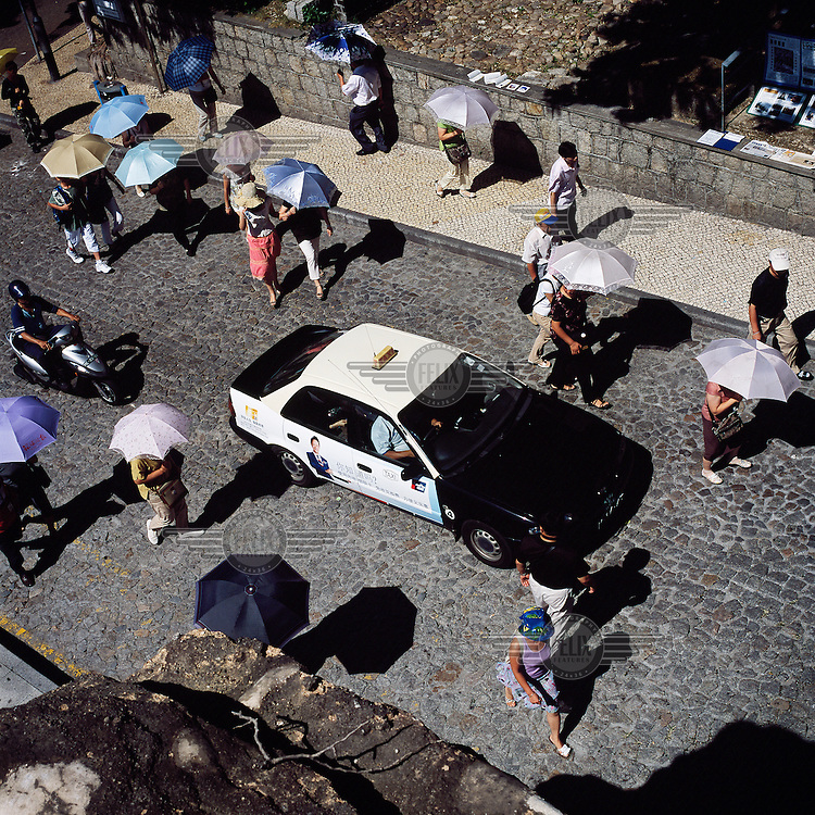 Tourists, protecting themselves from the sun beneath umbrellas, walking along one of Macau's cobbled streets.