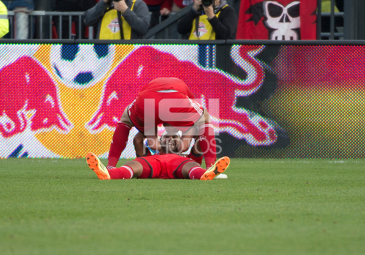 Toronto, Ontario - May 17, 2014: Toronto FC defender Bradley Orr #16 celebrates a goal by Toronto FC forward Luke Moore #27, lying on the field, during a game between the New York Red Bulls and Toronto FC at BMO Field. Toronto FC won 2-0.