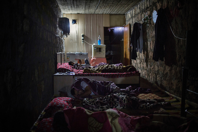 29/08/15. Shaqlawa, Iraq. -- The children of Sabah, 48, from Falluja, sleep inside a windowless room, in the basement of a residential complex. The complex was bought by a rich man from Falluja at the end of 2013. The man is now renting out the 16 apartments as well as the basement to displaced families for 250 usd each.
