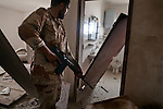 An anti-Gaddafi fighter searched an empty home, in the Seven Hundred neighborhood of Sirte, Libya, Oct. 7, 2011. Revolutionaries pressed in to Col. Muammar Gaddafi's hometown, encountering fierce resistance snipers, rocket-propelled grenades, and mortars.