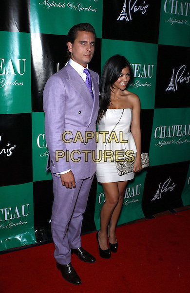 Scott Disick & Kourtney Kardashian .Scott Disick hosts a night at Chateau Nightclub inside Paris Las Vegas, Las Vegas, Nevada, USA, 2nd July 2011..full length purple suit white shirt tie  jacket couple strapless white zip ruffle peplum dress snakeskin snake clutch bag .CAP/ADM/MJT.© MJT/AdMedia/Capital Pictures.