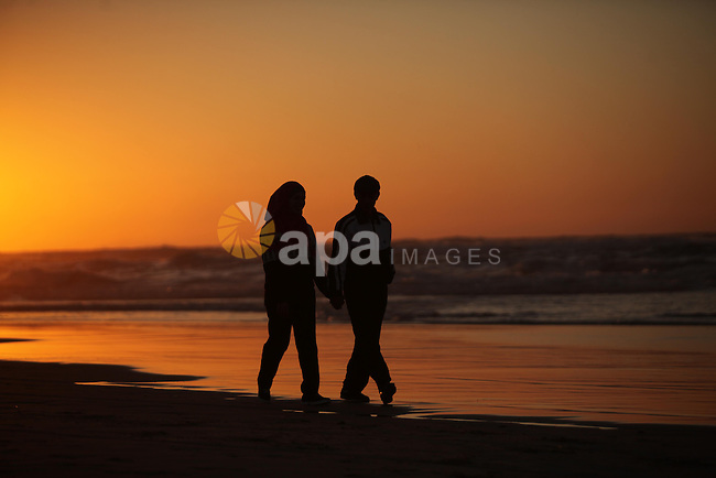 Palestinians walk on the beach of Gaza City, during the last sunset of 2016, on December 31, 2016. Photo by Ashraf Amra