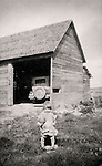 Adele Madelaine Michaud Brissette. 1930. Quebec. Child with chicken in front of old barn with car.