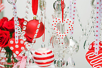 A collection of Christmas baubles and hearts is suspended from a crystal candelabra by coloured ribbon