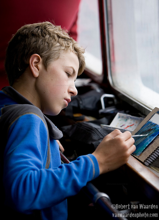 A young teenage man works on a watercolor painting of the Arctic landscape from a ship window. The man is part of the Cape Farewell Youth Expedition organized by the British Council of Canada.