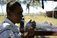 An elder man takes first breathe from his hand rolled cigarette during the end of year 2010 party of fishermen at Leonsberg, located northern part of Paramaribo. ....End of year 2010 celebrations on the streets of Paramaribo. Suriname is one of biggest consumer in South America that using firecrackers, fireworks ( also locally known as pagara ) for celebrations, especially for end of every years and also beginning of every new Chinese Years.