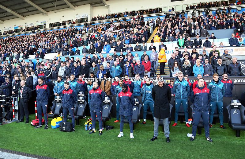 The Swansea bench observes a minute's silence during the Premier League match between Swansea City and Brighton and Hove Albion at The Liberty Stadium, Swansea, Wales, UK. Saturday 04 November 2017