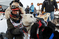 Marcelle Fressineau gives her lead dog a hug in the finish chute shorlty after finishing in 49th and last place at Nome on Saturday March 15 during the 2014 Iditarod Sled Dog Race.<br /> <br /> PHOTO (c) BY JEFF SCHULTZ/IditarodPhotos.com -- REPRODUCTION PROHIBITED WITHOUT PERMISSION